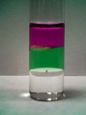 sample vial containing 3-phases, consisting of an organic layer (pink), water layer (green) and an asymmetric quaternary ammonium ionic liquid (clear) layer